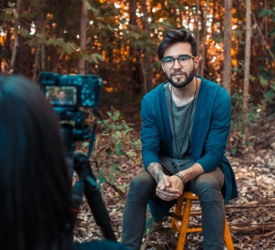 photo-of-a-man-sitting-in-front-of-a-camera-2531552